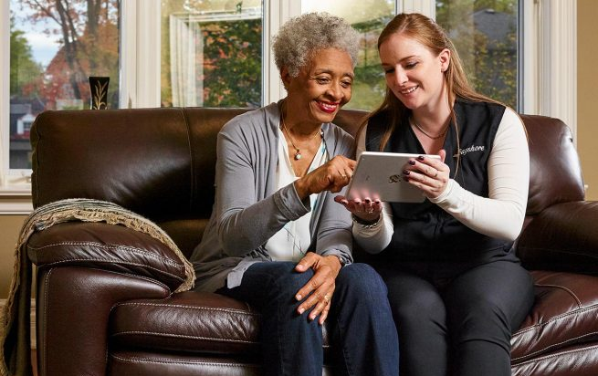 Caregiver with client on tablet